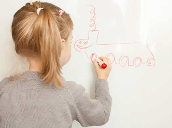 Little Girl Drawing On A Whiteboard
